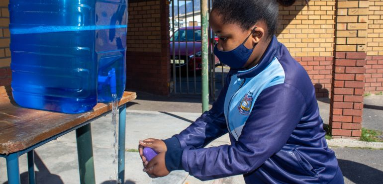 Ezam Bopape, a learner at Surrey Primary School using one of the soap bars donated to her school.